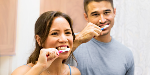 A Hawaiian man and woman are happily brushing their teeth.